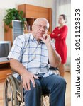 Small photo of sad elderly couple of woman and man with disability.