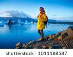 woman in bright yellow raincoat ...   Shutterstock . vector #1011188587