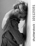 portrait of young beautiful girl in a coat longing near a wall - stock photo