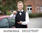 Small photo of Portrait Of A Handsome Male Valet Holding Car Keys Outdoors