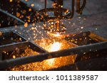 Small photo of Acetylene torch CNC auto machine cutting steel plate metalwork with bright sparks in factory.