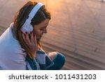 woman with headphones sitting... | Shutterstock . vector #1011431203