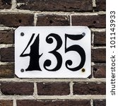 house number four hundred thirty-five on a brick wall - stock photo