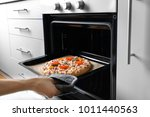 woman putting baking sheet with ... | Shutterstock . vector #1011440563