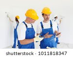 Small photo of Workers discuss renovation project using digital tablet