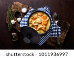 Small photo of Meat stew, chicken fillet in sauce with carrot in a cast iron pot, top view