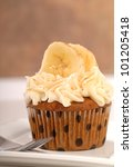 Delicious carrot cake cupcake with cream cheese frosting, bananas and cinnamon. - stock photo