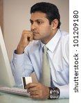 East Indian businessman shopping online with credit card - stock photo