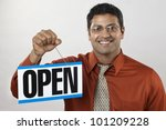 Happy East Indian business owner holding an Open Sign - stock photo