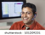 Smiling East Indian customer service rep with headset and computer monitor - stock photo