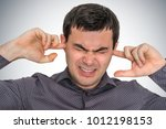 man closes ears with fingers to ... | Shutterstock . vector #1012198153