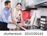 young couple looking at modern... | Shutterstock . vector #1012230163