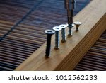 Small photo of Scattered screw screwed with screwdriver into the wooden plank - front view