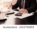 a business man using calculator ... | Shutterstock . vector #1012734853
