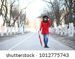pretty girl on a walk with red... | Shutterstock . vector #1012775743
