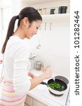 Young Asian woman to cook in the kitchen - stock photo