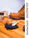 Small photo of Close-up of Premium Tan Brogue Leather Boot with Set of Cleaning Accessories,Wax and Cloth. Vertical Image Orientation