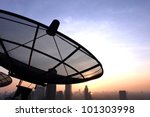 black antenna communication satellite dish over sunset sky in city - stock photo