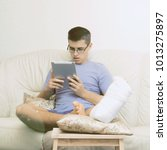 Small photo of A teenage boy with a broken leg alone at home does homework, reads a large and thick book, tablet and laptop. Leg in a cast. Disease.
