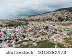the huge waste pile extends... | Shutterstock . vector #1013282173