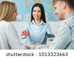 young couple in a tour agency... | Shutterstock . vector #1013323663