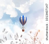 Small photo of Colorful aerostat flying among paper documents and over the blue cloudy sky. 3D rendering.