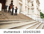 Small photo of Four well dressed professionals in discussion on the exterior steps of a building. Could be lawyers, government workers, business people etc.