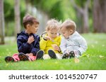 young boys sitting on grass in... | Shutterstock . vector #1014520747