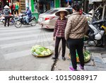Small photo of Hanoi Vietnam - Dec 2017: People bargaining for goods on a mobile bamboo basket found in the old quarter of Hanoi