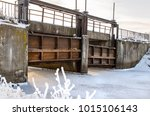 Small photo of Bridge in the form of a lock on a frozen river in winter. Hydrotechnical structure for regulating the water level on the river. Meliorative channel with a system of locks.