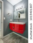 Small photo of Grey bathroom design in a freshly renovated home. Gray walls complementing a modern red vanity cabinet accented with oval sink.