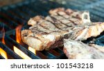 Steak on the grill with flames - stock photo