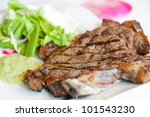Steak with marks on a white plate with some sallad - stock photo