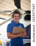 Small photo of Portrait Of Male Aero Engineer With Clipboard Carrying Out Check On Helicopter In Hangar