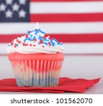 Red white and blue cupcake with american flag in background - stock photo