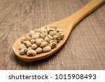 Small photo of Vigna unguiculata is scientific name of Black Eyed Pea legume. Also known as Goat Pea, California Blackeye and Feijao Fradinho. Spoon and grains over wooden table.