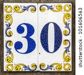 two crackled ceramic  tiles with house number thirty - stock photo