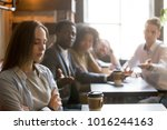 Small photo of Multiracial friends trying to make peace with insulted girl offended after bad joke, diverse young people apologizing aggrieved resentful drama queen woman sitting apart sulking at meeting in cafe