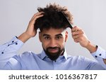 portrait of a young man combing ... | Shutterstock . vector #1016367817