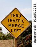 Small photo of Thru traffic merge left sign
