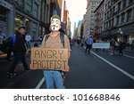 "NEW YORK CITY - MAY 1 : Occupy Wall Street's ""angry pacifist"" poses with his homemade sign while marching down Broadway in honor of International Workers' Day  on May 1 2012 in New York City. - stock photo"