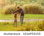 dad and daughter in the autumn... | Shutterstock . vector #1016953153