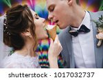 the bride and groom are eating... | Shutterstock . vector #1017032737