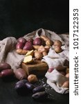 Small photo of Variety of raw uncooked organic potatoes different kind and colors red, yellow, purple on wooden cutting board with kitchen towels over black table. Dark rustic style