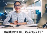 Small photo of Portrait of cheerful businesswoman satisfied with occupation sitting at desktop in office with modern technologies,smiling female designer happy about accomplished creative project looking at camera