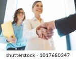 business women shaking hands in ... | Shutterstock . vector #1017680347