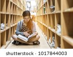 Small photo of Education-a girl are sitting to read a book in library ,she study hard for her exam -a girl 's serious to read book-the knowledge from library