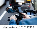 Small photo of Close up photo of motorcycle or maxi scooter driver in helmet use smartphone application to find geo location. Uses phone mobile technology in every day life. big city traffic jam and future app