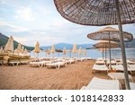 sun loungers on a beach in... | Shutterstock . vector #1018142833