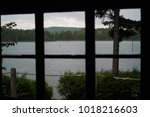 Small photo of View from inside a cabin looking towards a lake where a canoeist paddles.
